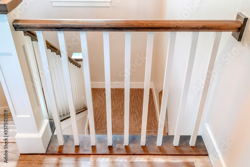 Fotomural U shaped stairway of home with brwon handrail supported by white balusters