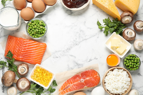 Flat lay composition with products rich in vitamin D on white marble table. Space for text