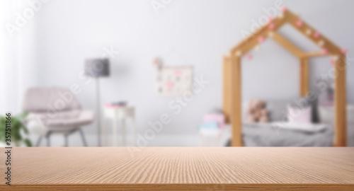 Tela Empty wooden table in baby room interior