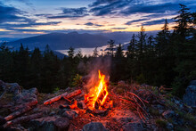 Warm Camp Fire On Top Of A Mountain With Beautiful Canadian Nature Landscape In Background During A Colorful Sunset. Taken On Bowen Island, Near Vancouver, British Columbia, Canada.
