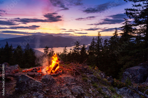 Fotografija Warm Camp Fire on top of a mountain with Beautiful Canadian Nature Landscape in background during a colorful Sunset