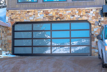 Garage Door With Glass Panes Reflecting A Snowy Hill Landscape Under Blue Sky