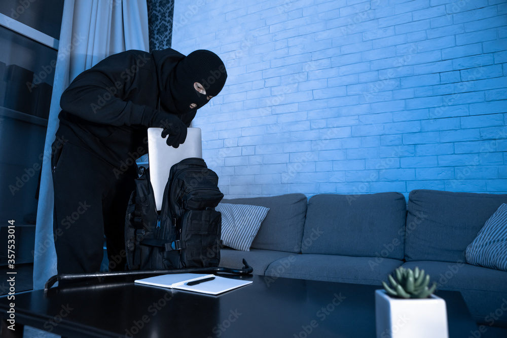 Fototapeta Intruder breaking in an apartment or office stealing pc