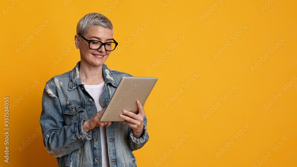 Fototapeta Modern Technologies For Leisure. Stylish Mature Lady Reading News On Digital Tablet