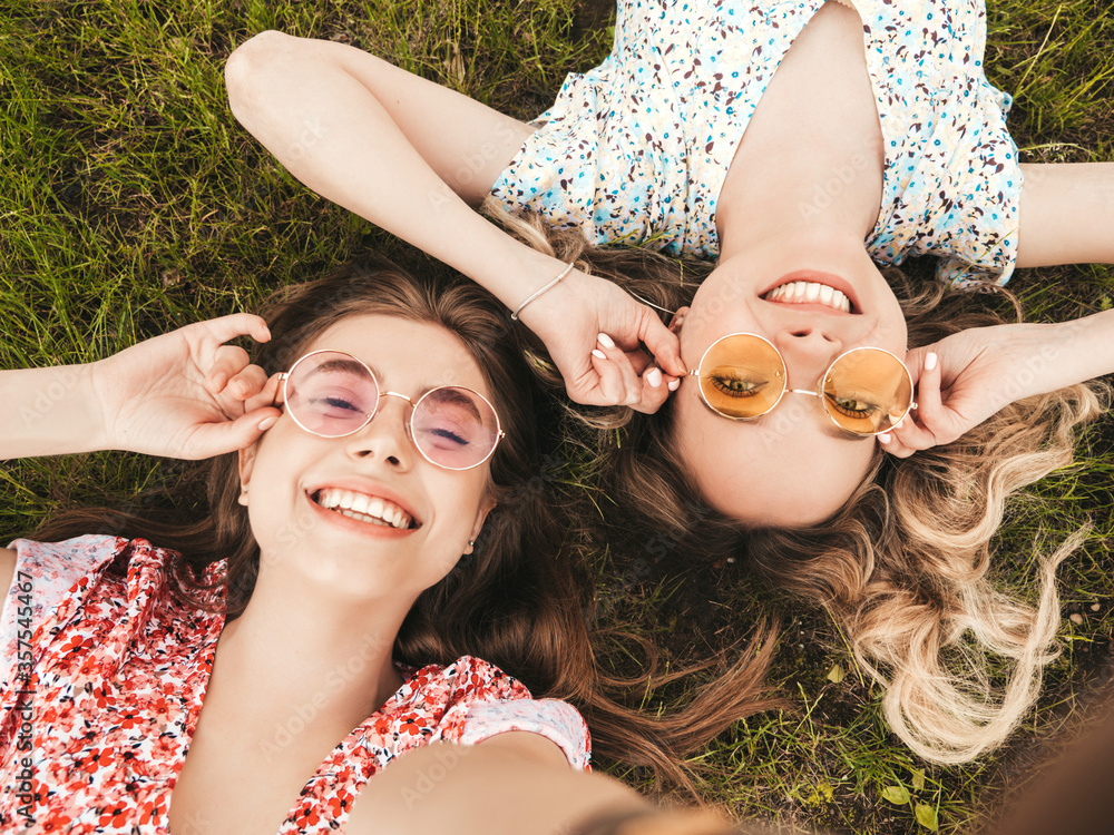Fototapeta Two young beautiful smiling hipster girls in trendy summer sundress.Sexy carefree women lying on the green grass in sunglasses.Positive models having fun.Top view