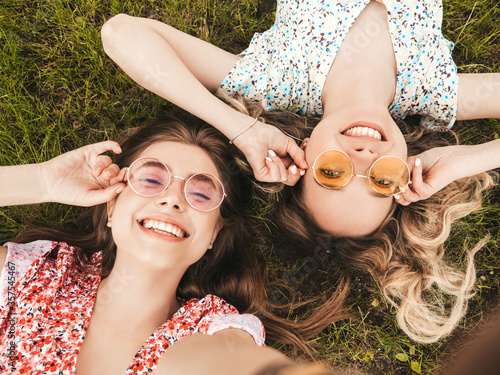 Fototapeta Two young beautiful smiling hipster girls in trendy summer sundress.Sexy carefree women lying on the green grass in sunglasses.Positive models having fun.Top view obraz