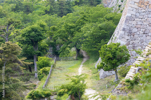 Narrow dirt path under ancient stone walls of Akashi Castle Wallpaper Mural