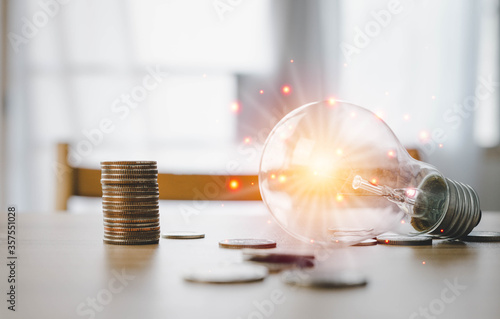 Fototapeta Light bulbs and coins placed on the work desk. Idea, working, innovation inspiration and success in life concept. obraz