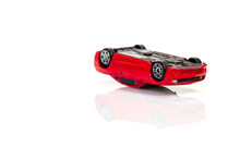 Driving Car In Alcoholic Intoxication: Red Toy Car Lies Upside Down On White Background