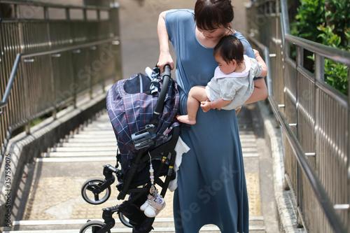 Fotografiet ベビーカーを持ち上げ階段を上る母親