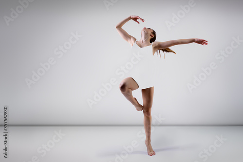 Young beautiful graceful woman with perfect slim sporty body dancing and jumping. Female beautiful contemporary dance. Ease of movement, youth, grace, joint pain relief and movement