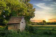 Stunning Landscape Image Of Old Derelict Farm Shed In Field During Beautiful Summer Sunset Over Distance
