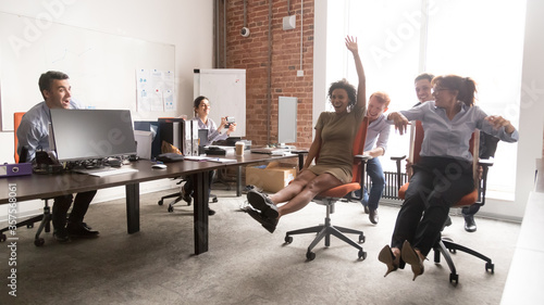 Fotografía Happy diverse colleagues having fun together, riding in office chair, excited em