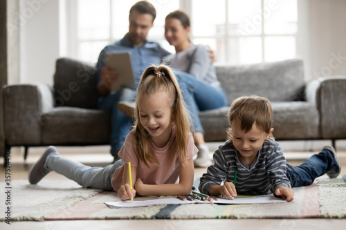 Obraz Little sister and brother playing on warm floor with underfloor heating while parents relaxing on couch in living room, cute girl and boy drawing with colorful pencils, enjoying leisure time - fototapety do salonu