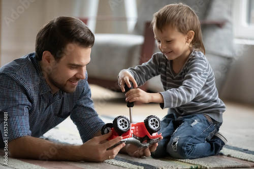 Happy father and little son playing with toy car together close up, sitting on warm floor with underfloor heating, cute preschool boy using screwdriver, having fun with dad, enjoying weekend at home