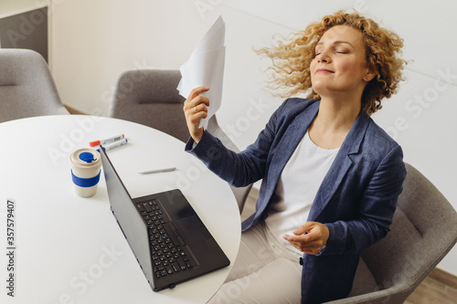 Adult young pretty business woman refreshing with a office papers, working at her office in summer time Wallpaper Mural