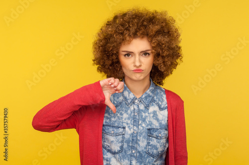 I don't like this! Portrait of upset woman with curly hair in casual outfit standing with thumbs down gesture, expressing disapproval, criticizing bad service Canvas