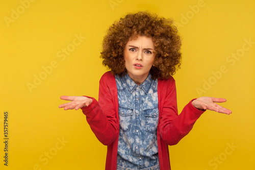 Obraz na plátně What do you want? Portrait of confused angry woman with curly hair raising hands in indignant gesture, expressing misunderstanding, having conflict
