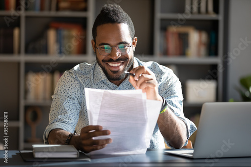 African student guy sitting at desk holding papers printed tasks perform test prepares for entrance exams enjoy process of study Tableau sur Toile