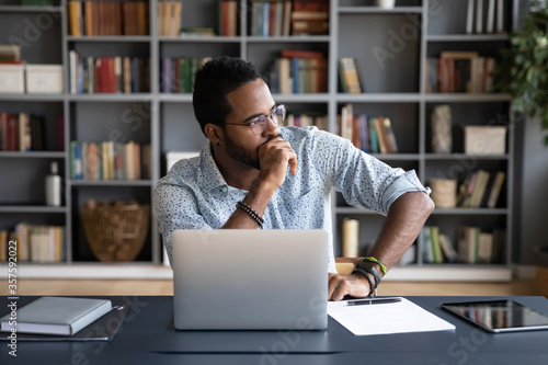 Thoughtful doubtful African businessman in tension sitting at workplace desk nea Fototapet