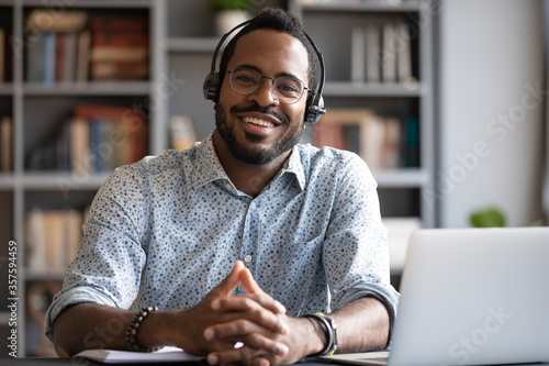 Fotografía African man wear headset sit at workplace desk smile looking at camera, company consultant portrait, distant communication with client