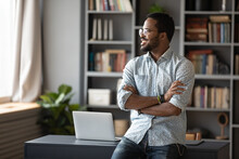 Happy Confident Young African Businessman Freelancer Standing Near Workplace Desk In Modern Office With Arms Crossed Look Out The Window Dreaming About New Career Opportunities And Great Future Vision