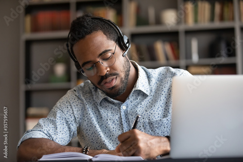 Focused young serious african ethnicity businessman wear headset writes notes in Canvas