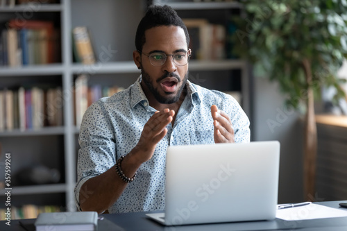 African guy sit at desk looks with amazement at laptop screen open mouth gawp at Canvas Print