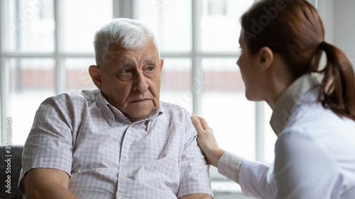 Fototapeta Female doctor comforting upset older patient at meeting, touching shoulder, expr