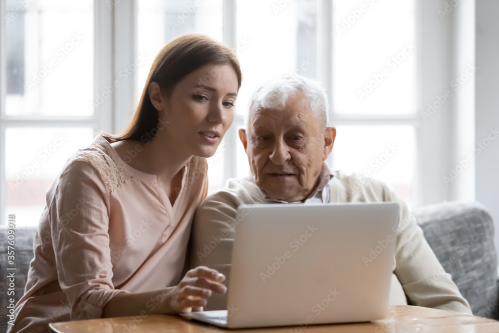 Fototapeta Caring grownup daughter teaching elderly father to use laptop, young woman and mature man looking at computer screen, sitting on couch at home, watching movie, making video call or shopping online