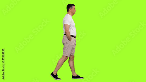 Cuadros en Lienzo Side view of a man in shorts and white t-shirt walking on green screen backgroun