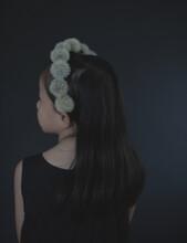 Rear View Of Girl Wearing Dandelion Fluffs Headband Standing Indoors