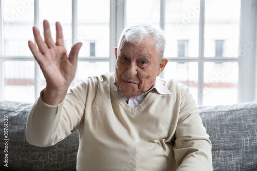 Head shot portrait happy mature man waving hand, saying hello, looking at camera Fotobehang