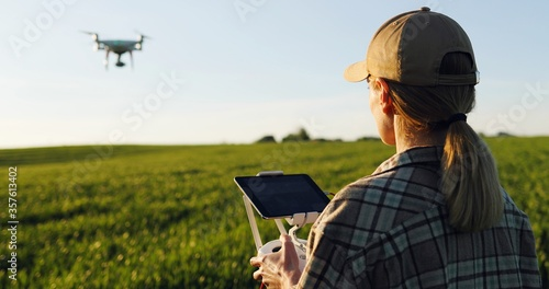 Close up of rear of Caucasian woman farmer in hat standing in green wheat field and controlling of drone which flying above margin Wallpaper Mural