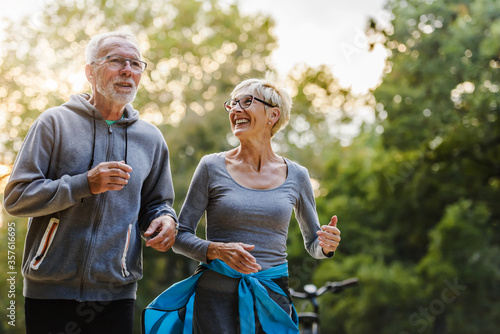 Smiling senior couple jogging in the park Canvas Print