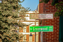 Black Wall Street And N Greenwood Avenue Street Signs - Closeup - In Tulsa Oklahoma With Bokeh Background