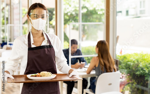 Fototapeta Asian waitress serving food new normal. obraz
