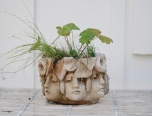 Stone Flowerpot Of Many Faces