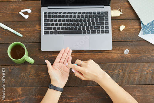 Fototapeta Top down view at unrecognizable young woman using hands sanitizer while using laptop at home office, copy space obraz