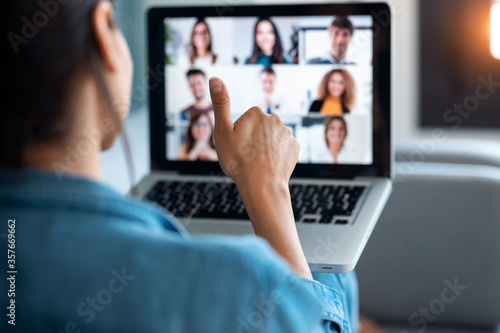 Obraz Business woman making video call and showing thumb up to laptop on the online briefing while sit on sofa at home. - fototapety do salonu
