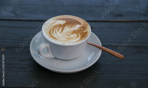 Cappuccino in cup with saucer and spoon, dark background Fototapete