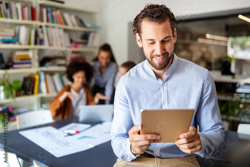 Smiling designer using his tablet pc while team works behind