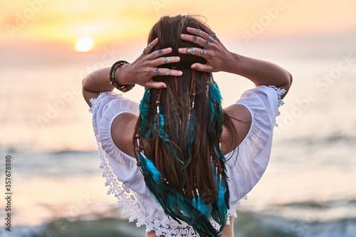 Hippie woman wearing blue feathers in long hair, silver rings with stone and white blouse stands back at sunset Fototapeta
