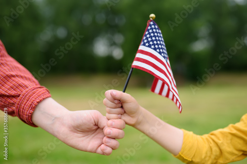 Young woman and little child holding american flag on grey background. Independence Day concept. National holiday.