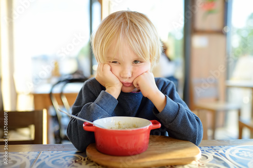 Fotografie, Tablou Little child sitting the table in cafe or restaurant and doesn't want to eat