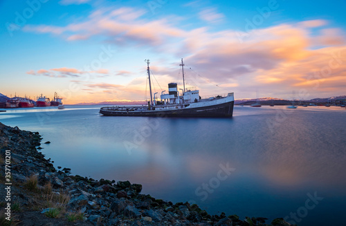 Fotografie, Obraz Long exposure of an anchored boat in the harbor of Ushuaia at sunset, Beagle Channel, Argentina