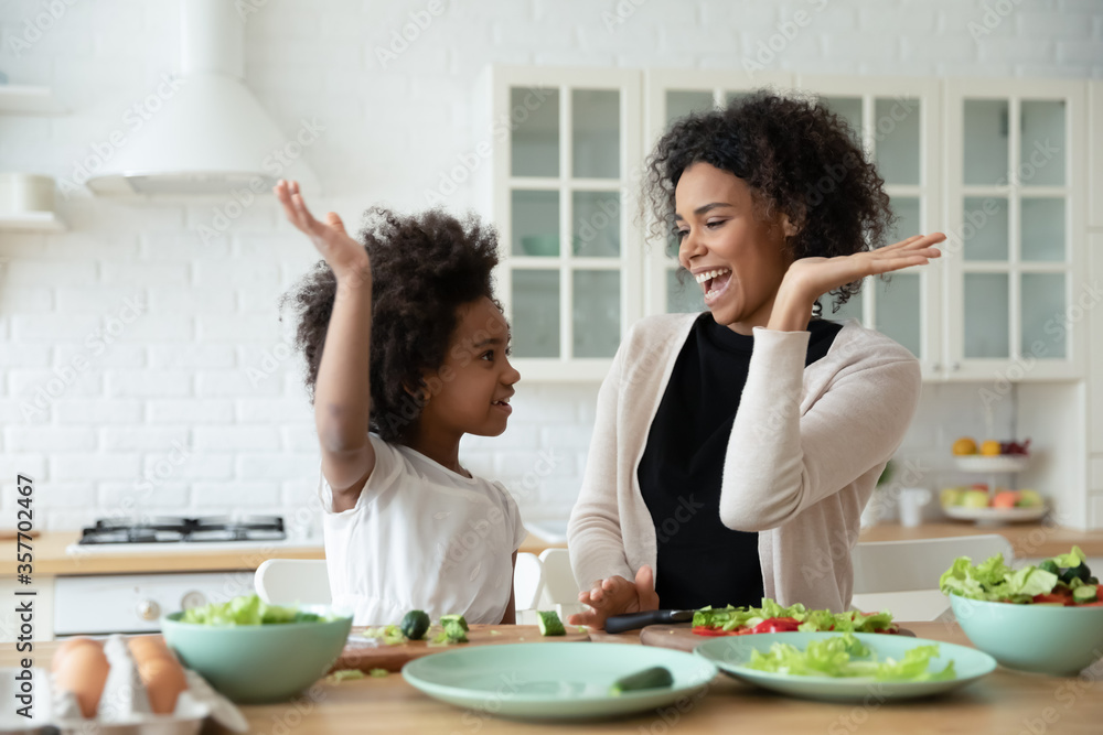 Fototapeta Excited African mom give high five gesture to little adorable mixed-race daughter family cook together dinner healthy food vegetarian salad. Teach kid, happy motherhood, share cookery skills concept