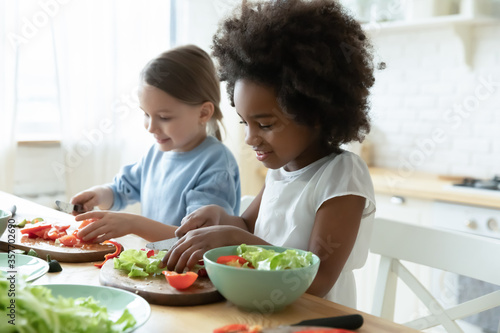 Fototapeta African and Caucasian little girls best friends cooking together in modern kitchen