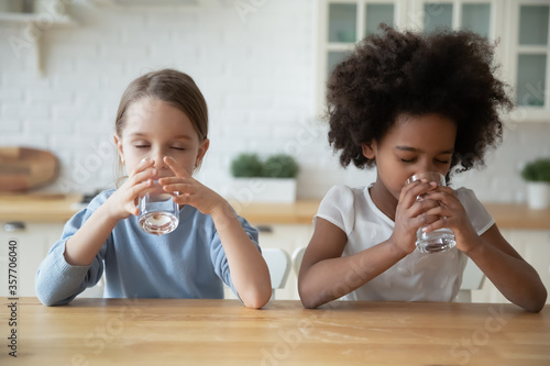 Fototapeta Two multi-ethnic dehydrated little girls reducing thirst drinking natural clean water seated at table in domestic kitchen. Healthy lifestyle, good life habit, daily body organism refreshment concept obraz na płótnie