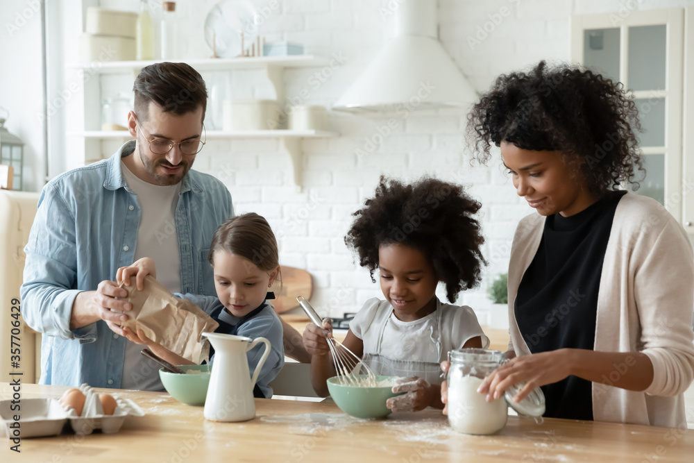 Fototapeta Multi racial full family cooking pastries gathered together in kitchen mixing products fresh ingredients eggs flour and milk make dough preparing holiday cake. Lifestyle, parenthood, cookery concept